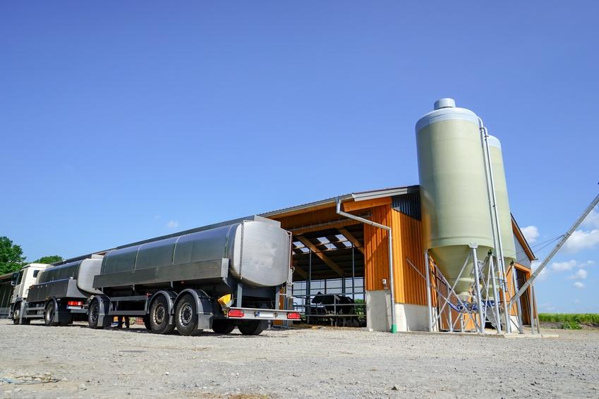 Milchwagen mit Anhänger vor einem neuen Kuhstall